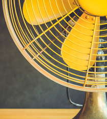 A yellow fan sits on a yellow table.