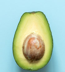 An avacado sliced in half casting a slight shadown on a light blue background
