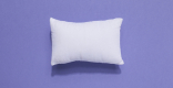 A fluffy white pillow sits in the center of a purple background.