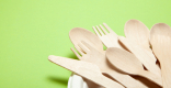 Bamboo forks, knives and spoons sit in a white paper place on a green background.