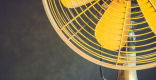 A yellow metal fan sits on a wood table.